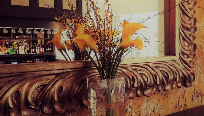 Yellow flowers in a glass vase on the fire place mantel