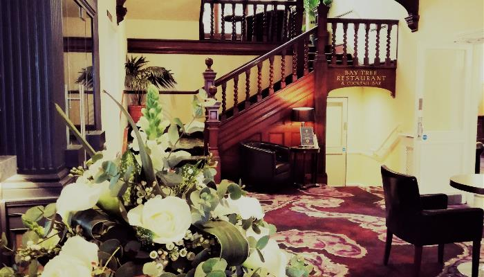Wooden stairwell, wooden pillars, white flowers & deep red patterned carpets