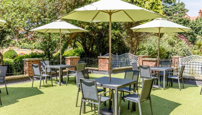 Outdoor dining & drinking area with black tables & chairs each with a white parasol