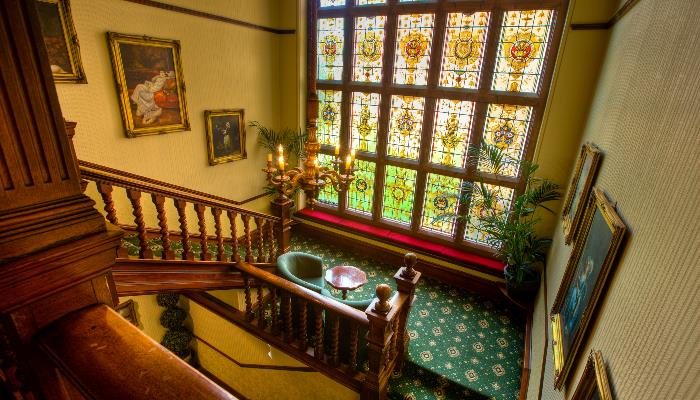 Grand stairwell with stained glass windows, paintings on the wall & green carpet