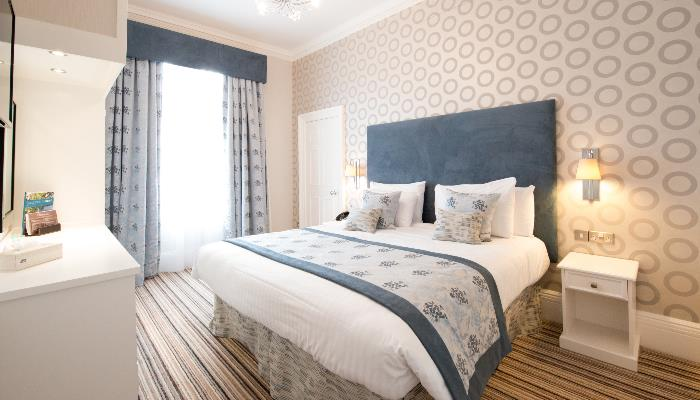 Bright room with double bed with white duvet & blue blacket over the top patterned with flowers