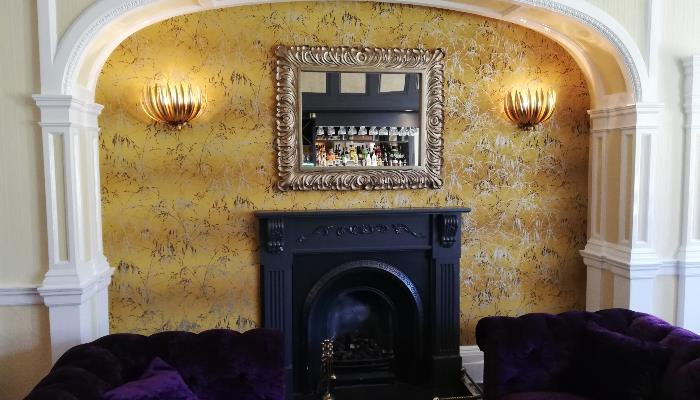 Black fireplace against a floral patterned yellow wall with an ornate mirror mounted above